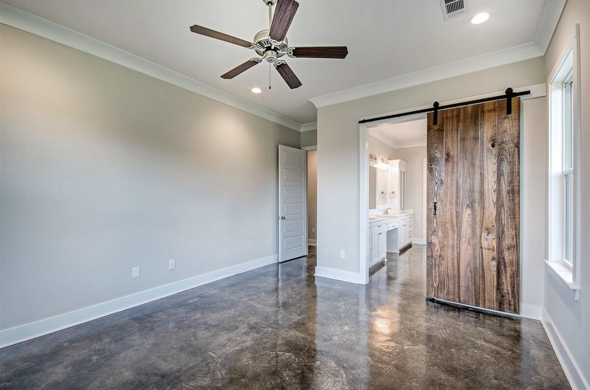 The primary bedroom includes a private bath enclosed in a sliding barn door.