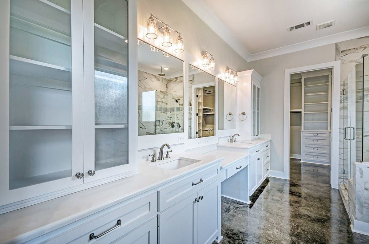 Primary bathroom with dual vanity and a walk-in closet.