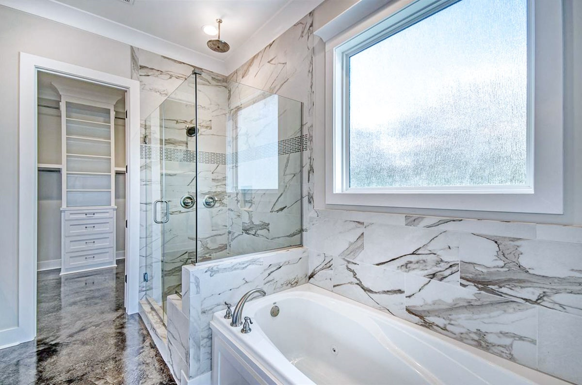 There's also a walk-in shower and a deep soaking tub fixed under the picture window.