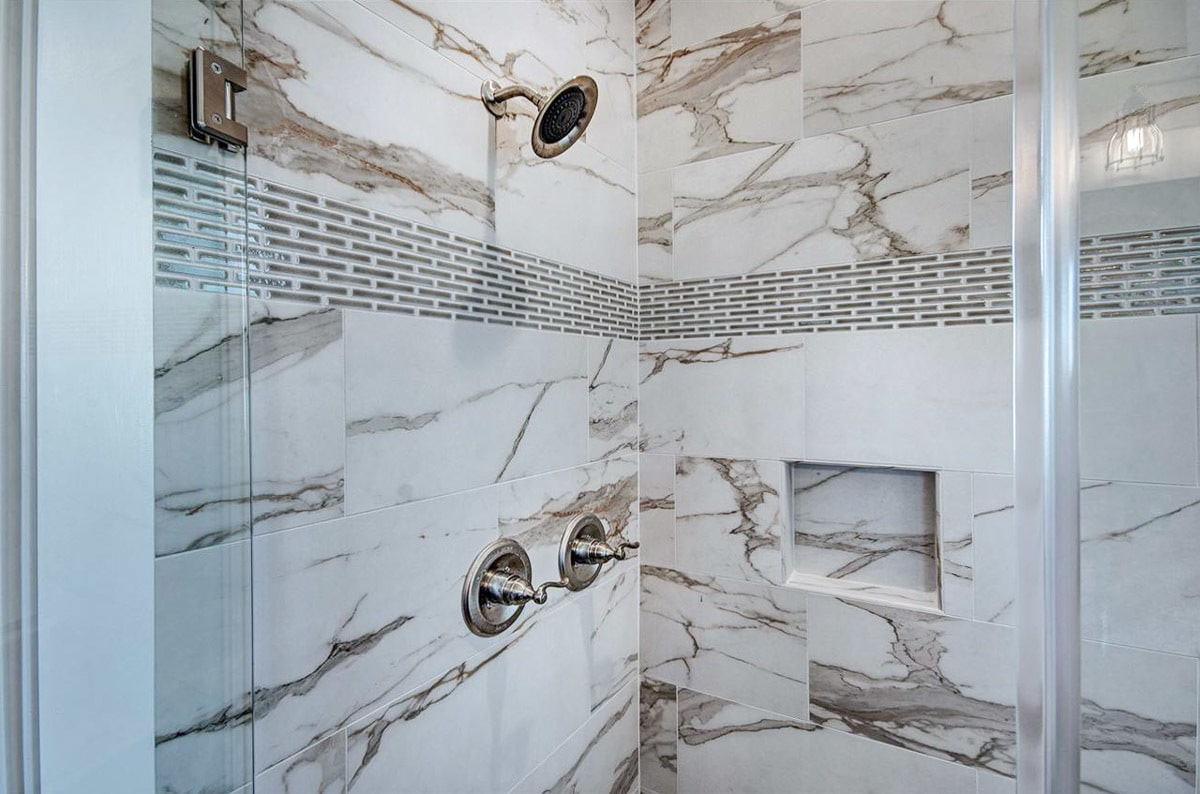 Closeup view of the walk-in shower showing its marble tiled walls, chrome fixtures, and an inset shelf.