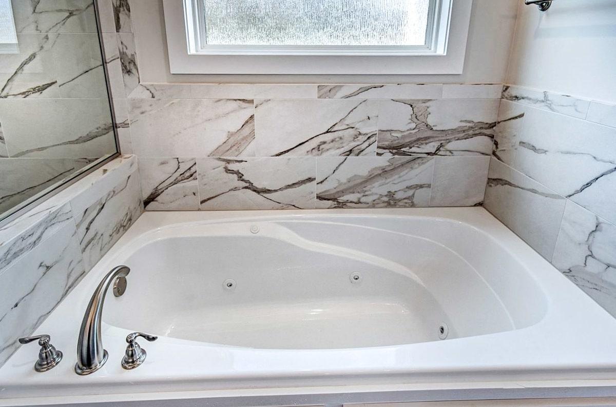 The bathtub has also chrome fixtures and a marble-tiled backsplash.