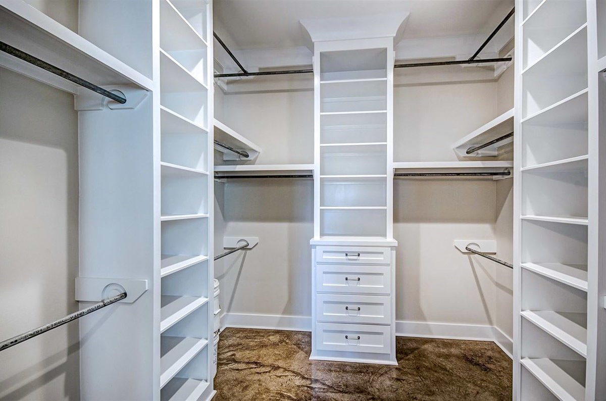 Walk-in closet with white built-in shelves and pole racks.