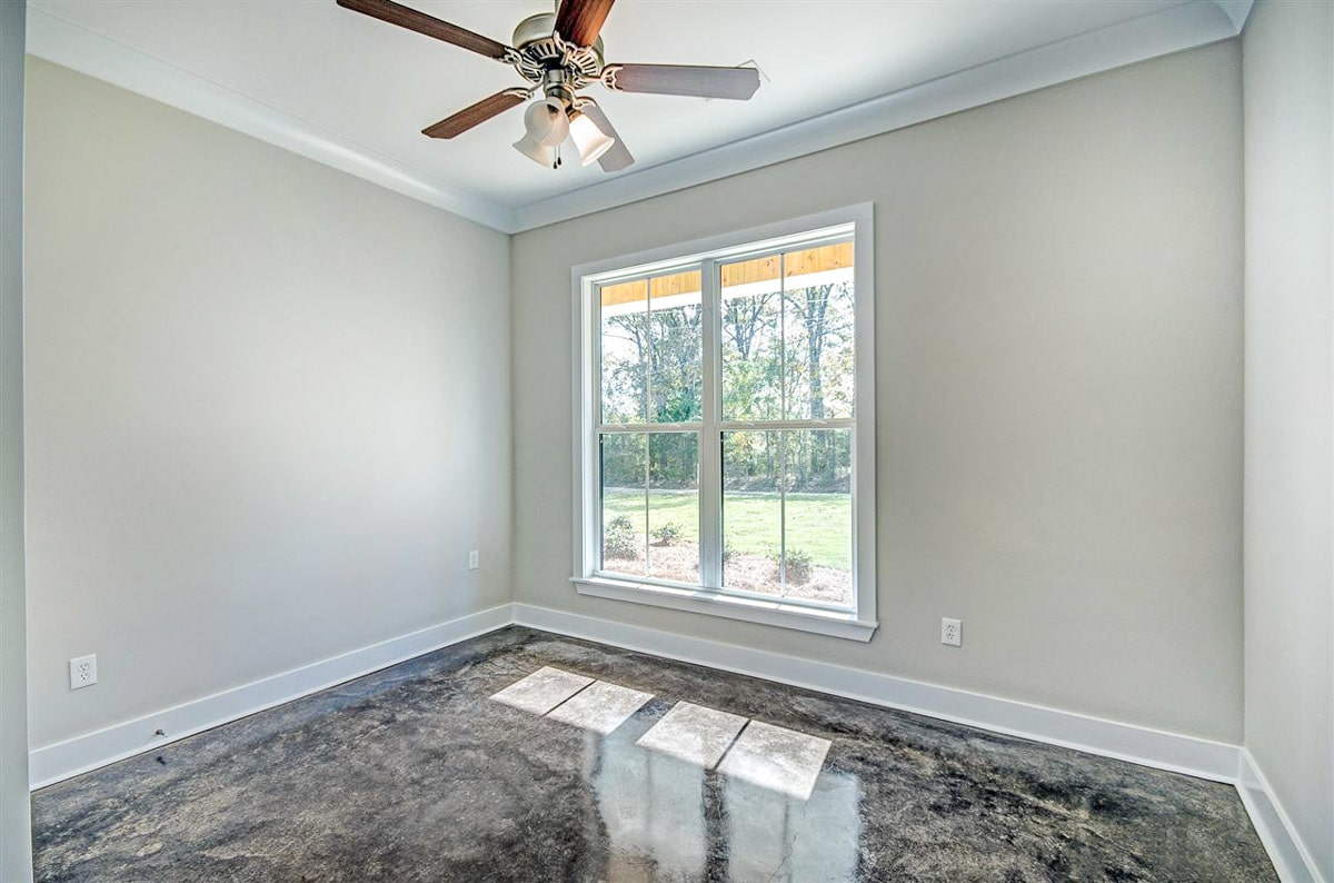 Bedroom with gray walls, a ceiling fan, and a white framed window overlooking the yard.