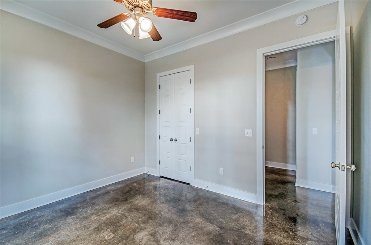 This bedroom also includes a walk-in closet concealed in a white double door.
