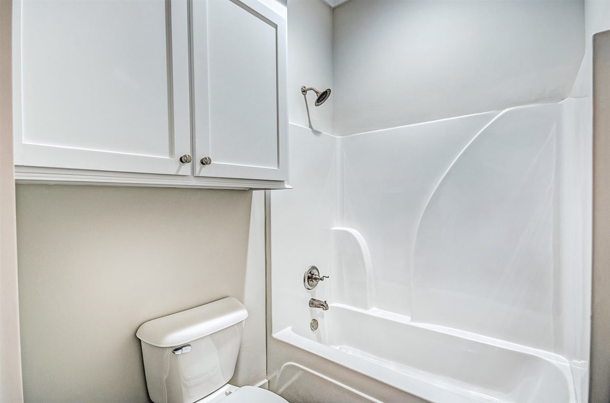 There's also a tub and shower combo and a toilet placed under a white cabinet.