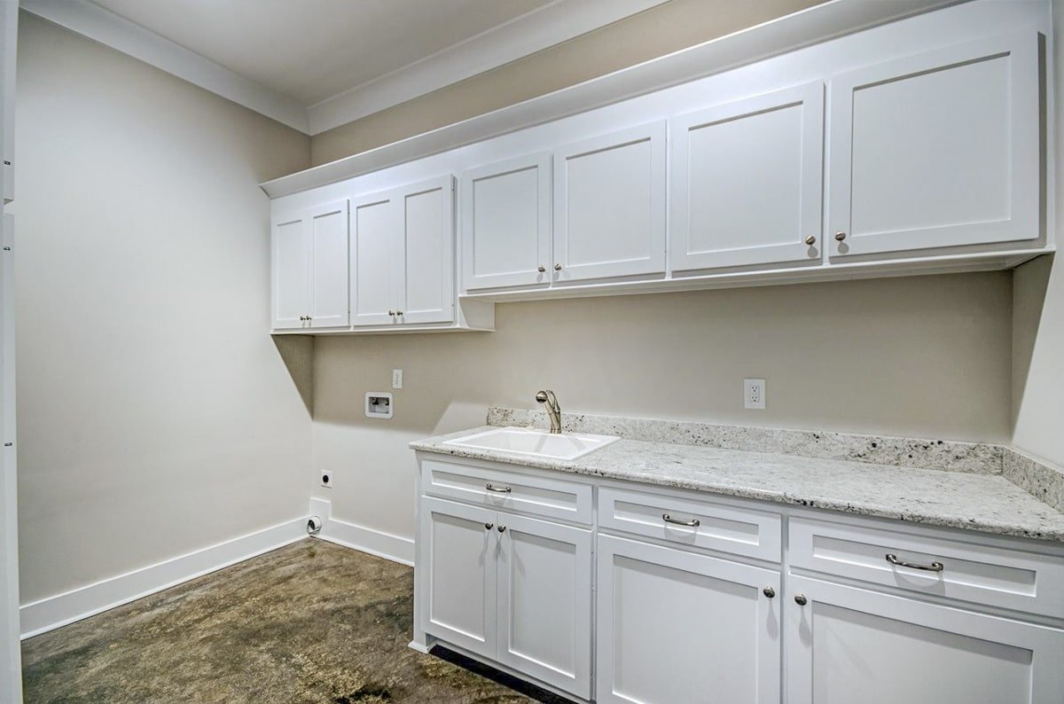 Utility room with white cabinets, granite countertops, and a porcelain sink.