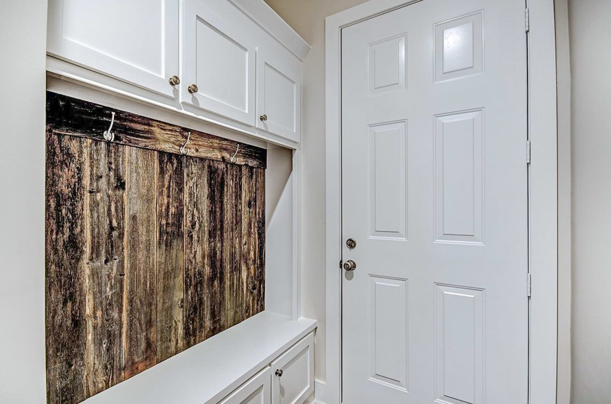 Mudroom with a coat rack, white cabinets, and a built-in bench.