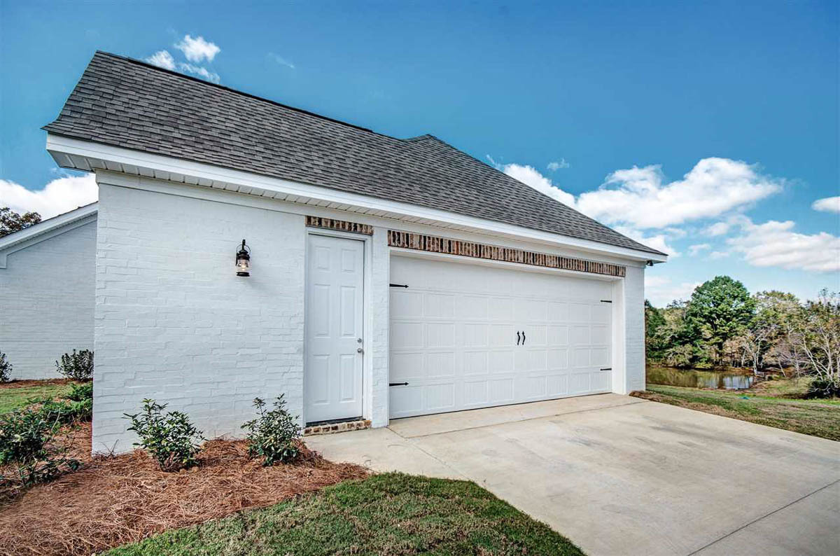 Side-entry garage with brick exterior, tiled roof, white garage door, and a man door leading to its storage room.