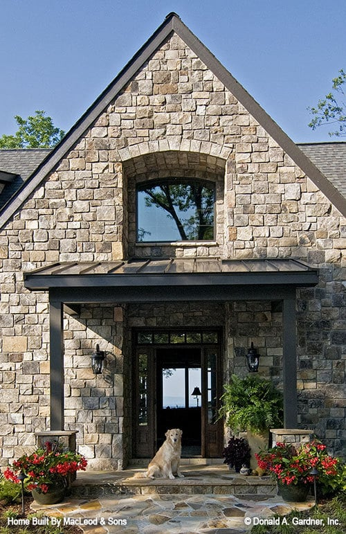 Home entry with a covered porch and a wooden front door surrounded by sidelights and transom windows.