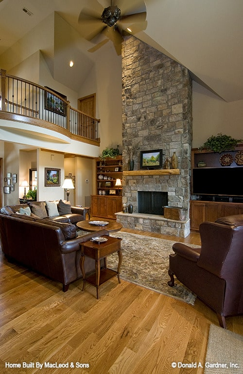 Living room with a high vaulted ceiling, leather seats, and a stone fireplace flanked by wooden built-ins.