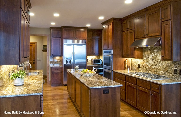 The kitchen is equipped with granite countertops, stainless steel appliances, wooden cabinetry, and a center island.