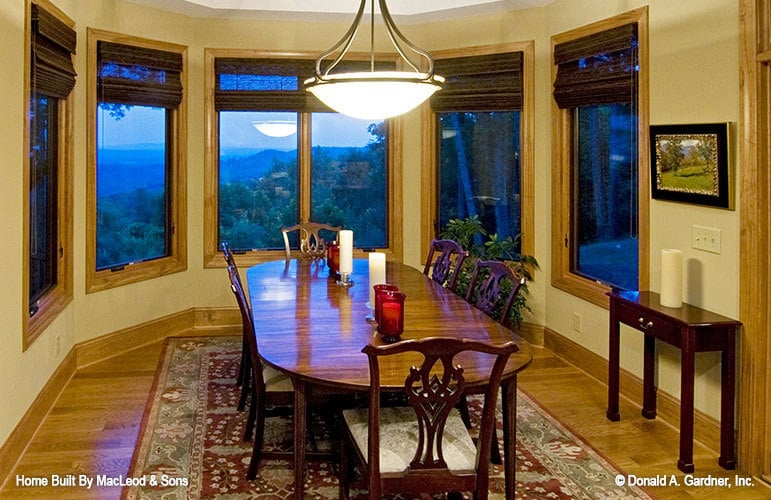 Dining area with a bay window and an oval dining set sitting on a bordered area rug.