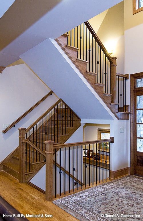 Wooden staircase with wrought iron railings leading to the basement and the upper level.