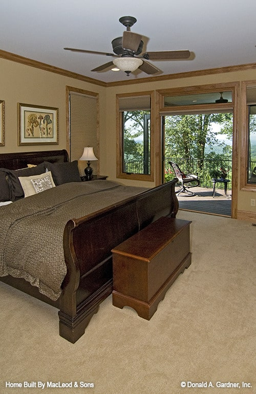 The primary bedroom has carpet flooring, dark wood furnishings, and direct porch access.