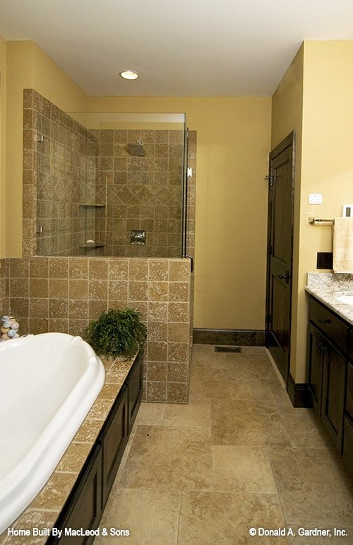 Primary bathroom with a wooden vanity, drop-in bathtub, and a walk-in shower.
