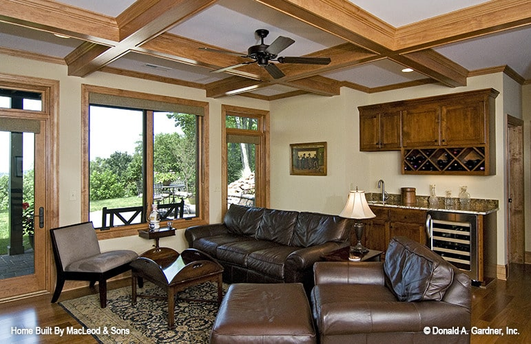 Recreation room with coffered ceiling, leather seats, and a wet bar with wine fridge and shelves.