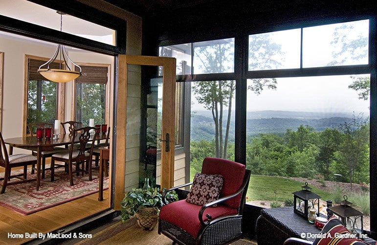 The screened porch off the dining area has cushioned wicker seats and overlooks a breathtaking mountain view.