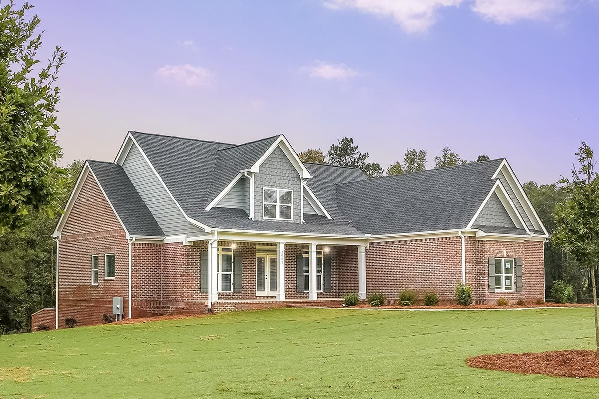 Rear exterior view showing the red brick exterior and a covered porch topped with a gable dormer.