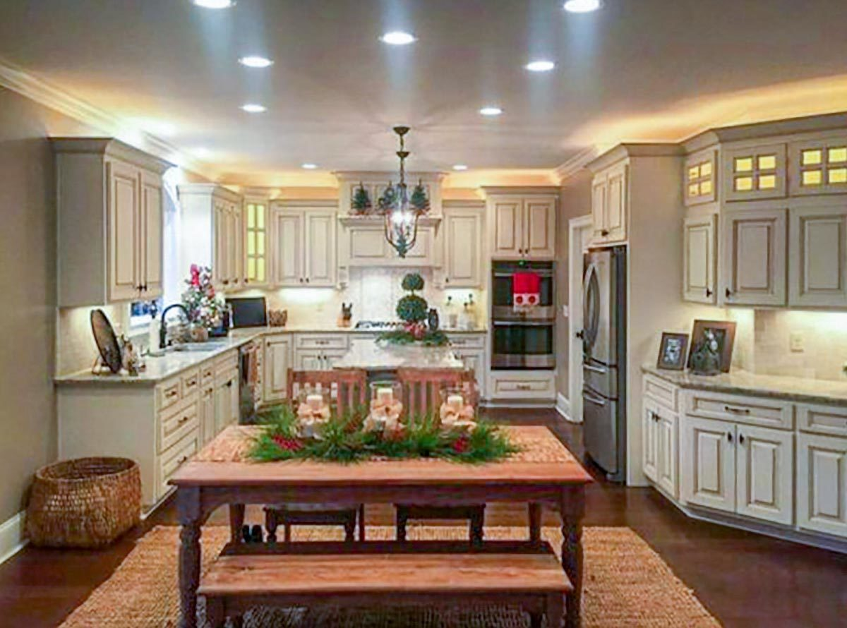 The eat-in kitchen is equipped with stainless steel appliances, granite countertops, cream cabinetry, and a wooden dining set.