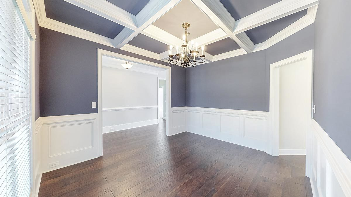 Formal dining room with coffered ceiling and gray walls adorned with white wainscoting.
