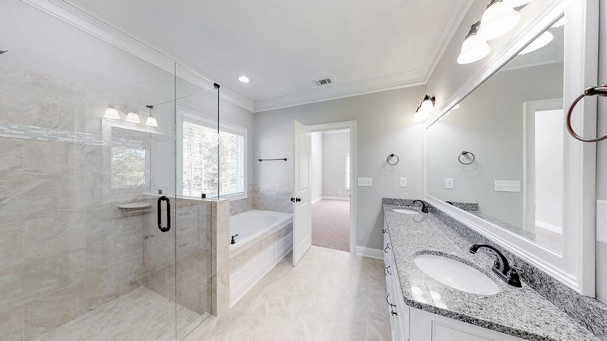 Primary bathroom with a walk-in closet, drop-in bathtub, and double vanity paired with a large rectangular mirror.