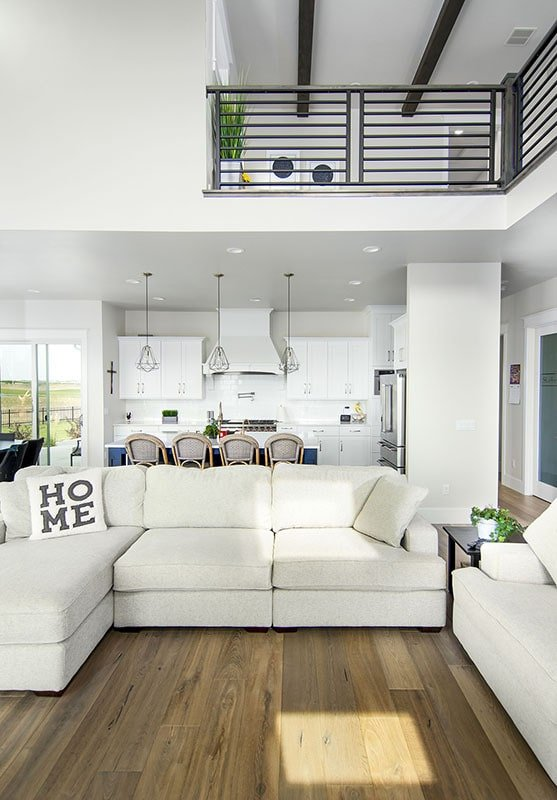 Across the kitchen is the living area with beige sofas over wide plank flooring.