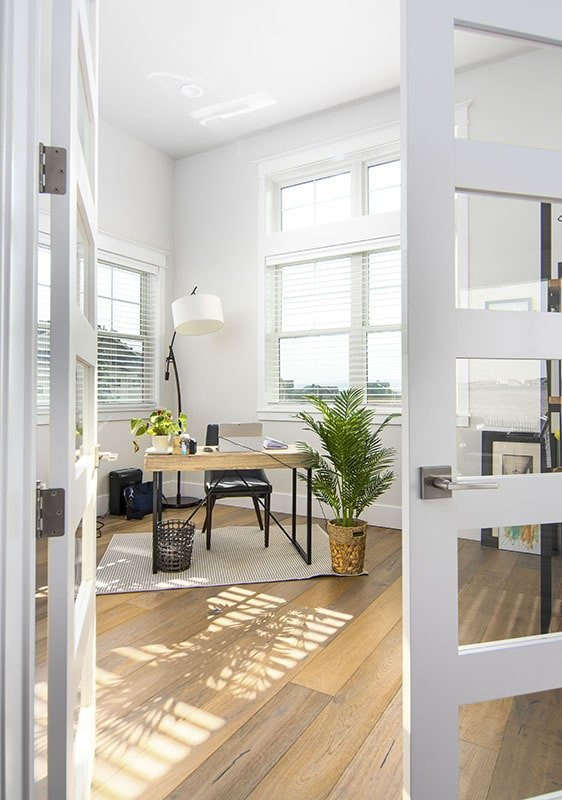 Home office with a french door, a wooden desk, upholstered chair, and a drum floor lamp.