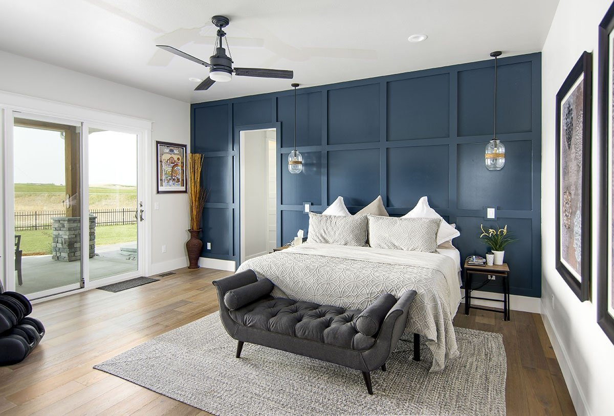 Primary bedroom with a stunning blue paneled accent wall, a tufted bench complementing the bed, and covered porch access.