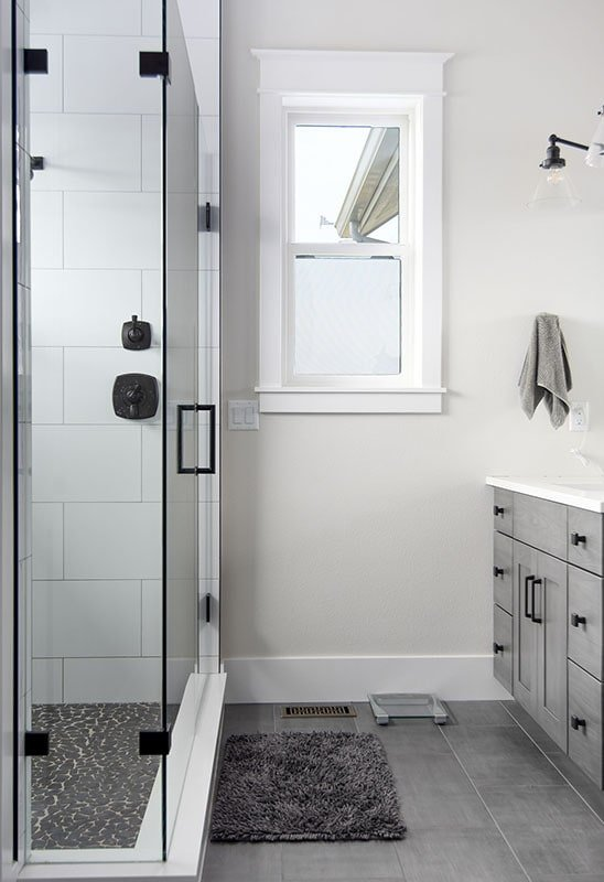 The primary bathroom offers light gray vanity and a walk-in shower.