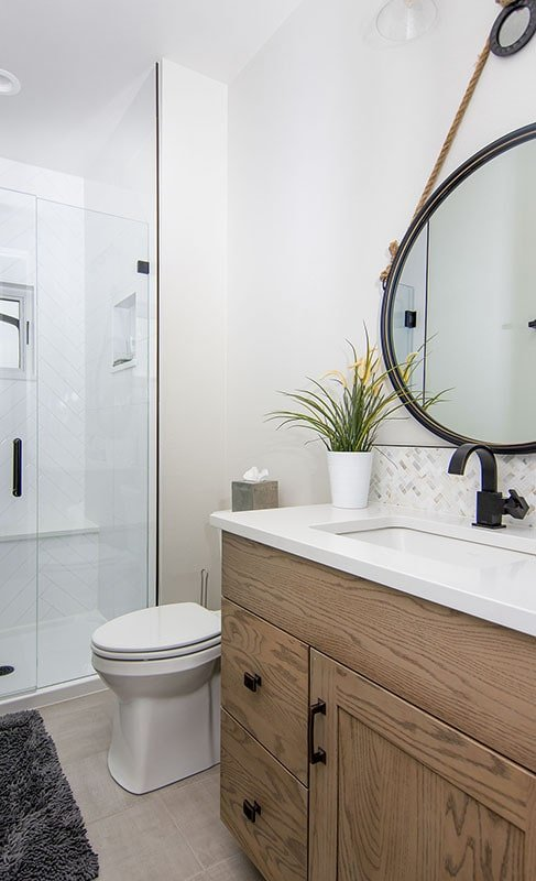 This bathroom includes a sink vanity, a toilet, and a walk-in shower with a tiled bench.