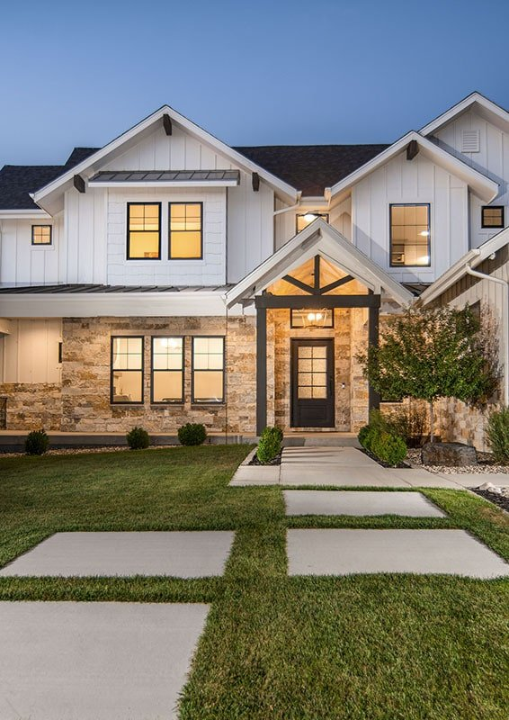 Home entry with stone walls, gable roofline, and dark wood trims that match the rustic front door.