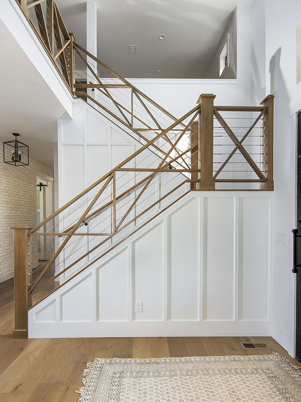 Staircase framed with wooden railings leading to the bedrooms upstairs.