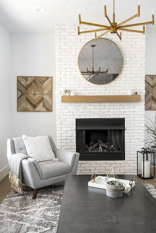 A close-up look at the brick fireplace adorned with a round brass framed mirror.