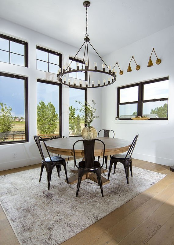 The dining area offers a round dining set and a wrought iron chandelier.