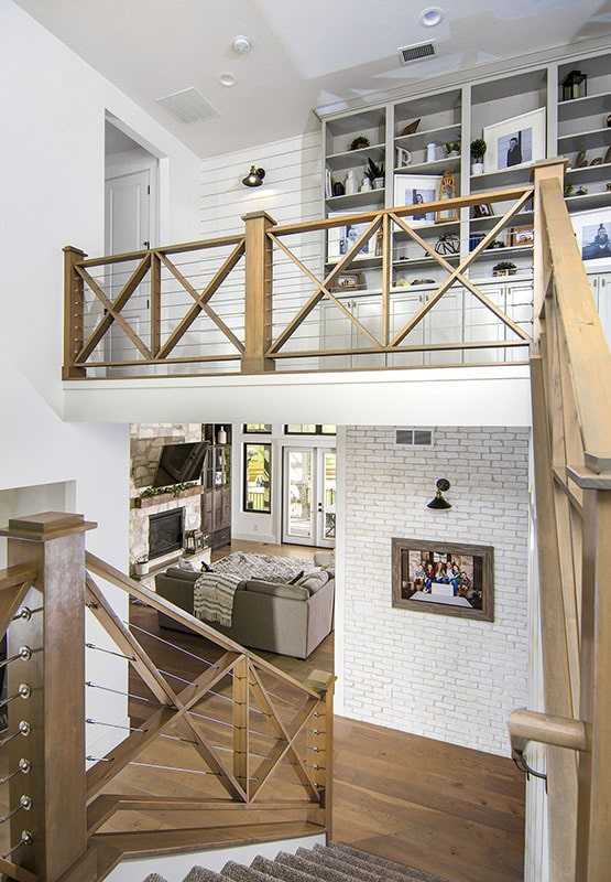 The staircase leads to the second-floor balcony filled with a built-in cabinet.