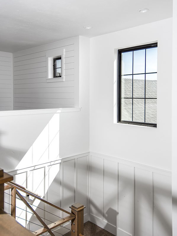 The staircase landing has a black aluminum-framed window that invites natural light in.