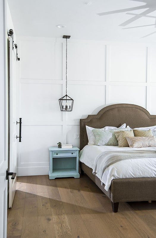 The brown upholstered bed is paired with a blue nightstand and a caged pendant light.