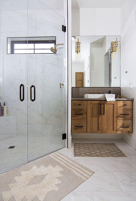 The primary bathroom offers a floating vanity and a corner shower enclosed in glass hinged doors.