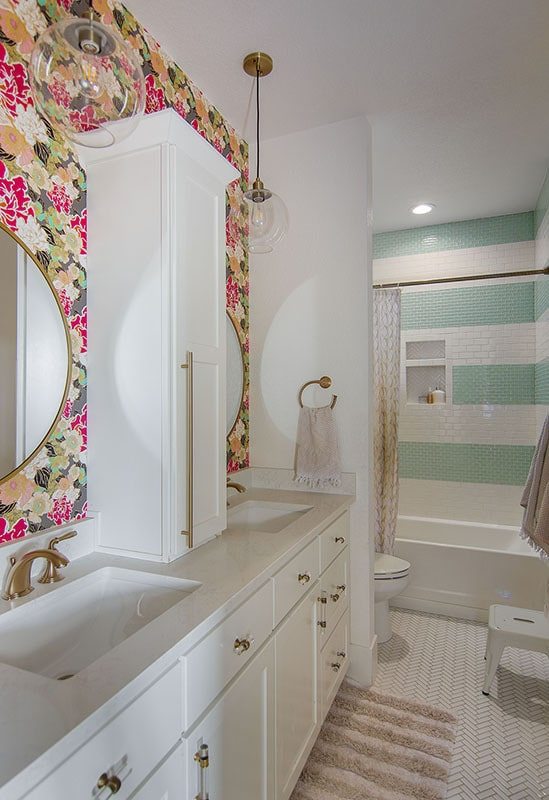 Bathroom with tub and shower combo, a toilet, and dual-sink vanity accented with floral wallpaper.