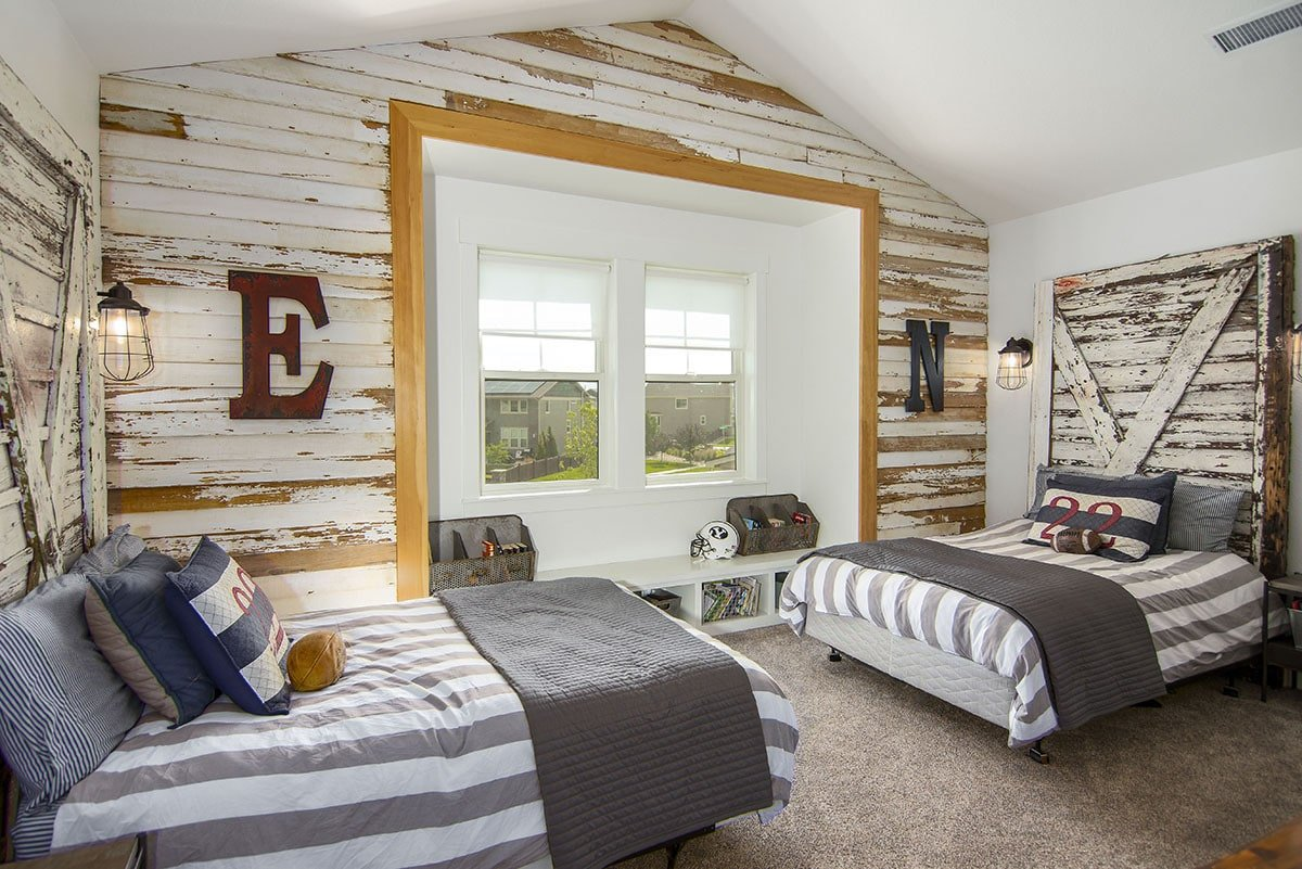 Distressed wood paneled accent wall along with matching headboards bring a rustic vibe to this bedroom.