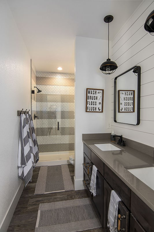This bathroom offers dual sinks, a toilet, and a walk-in shower clad in hex tile walls.