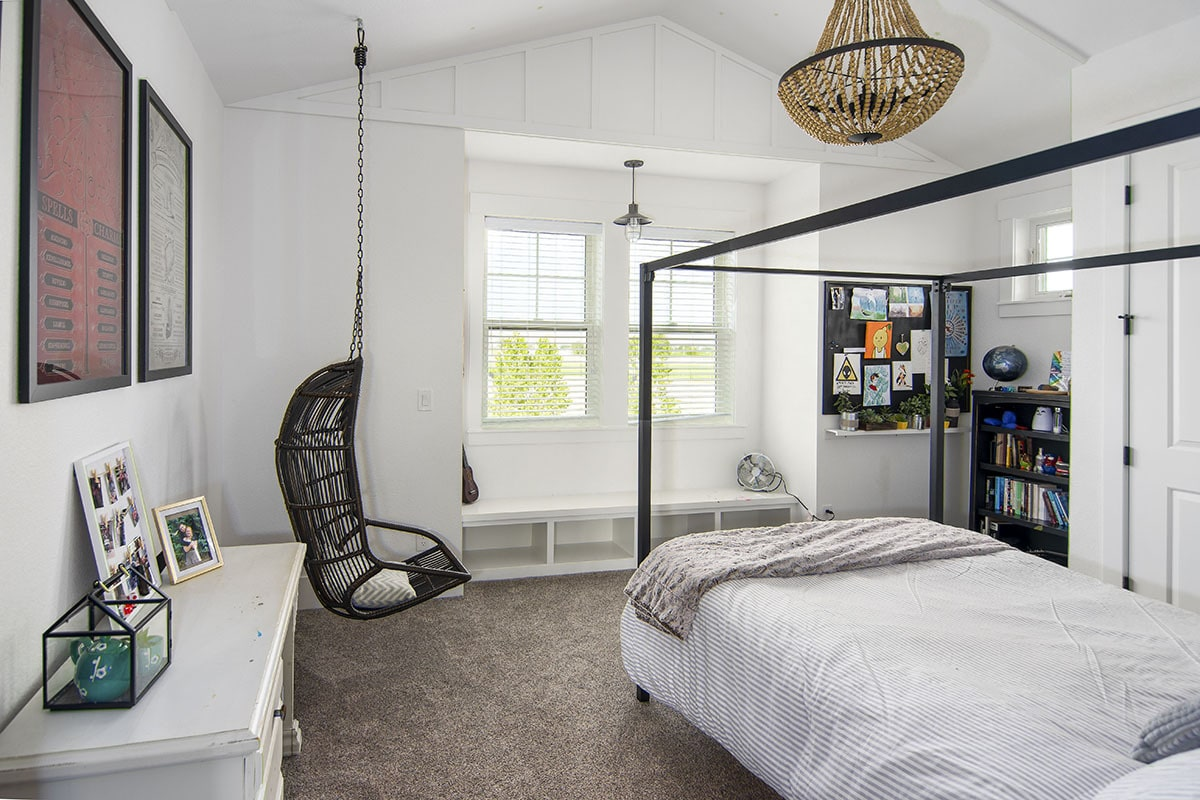 Bedroom with cathedral ceiling, window seat nook, a canopy bed, and a hanging chair.