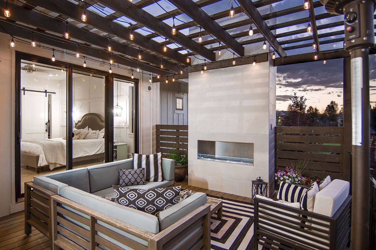 Covered porch with an outdoor fireplace, cushioned seats, and a trellis roof adorned with string lights.