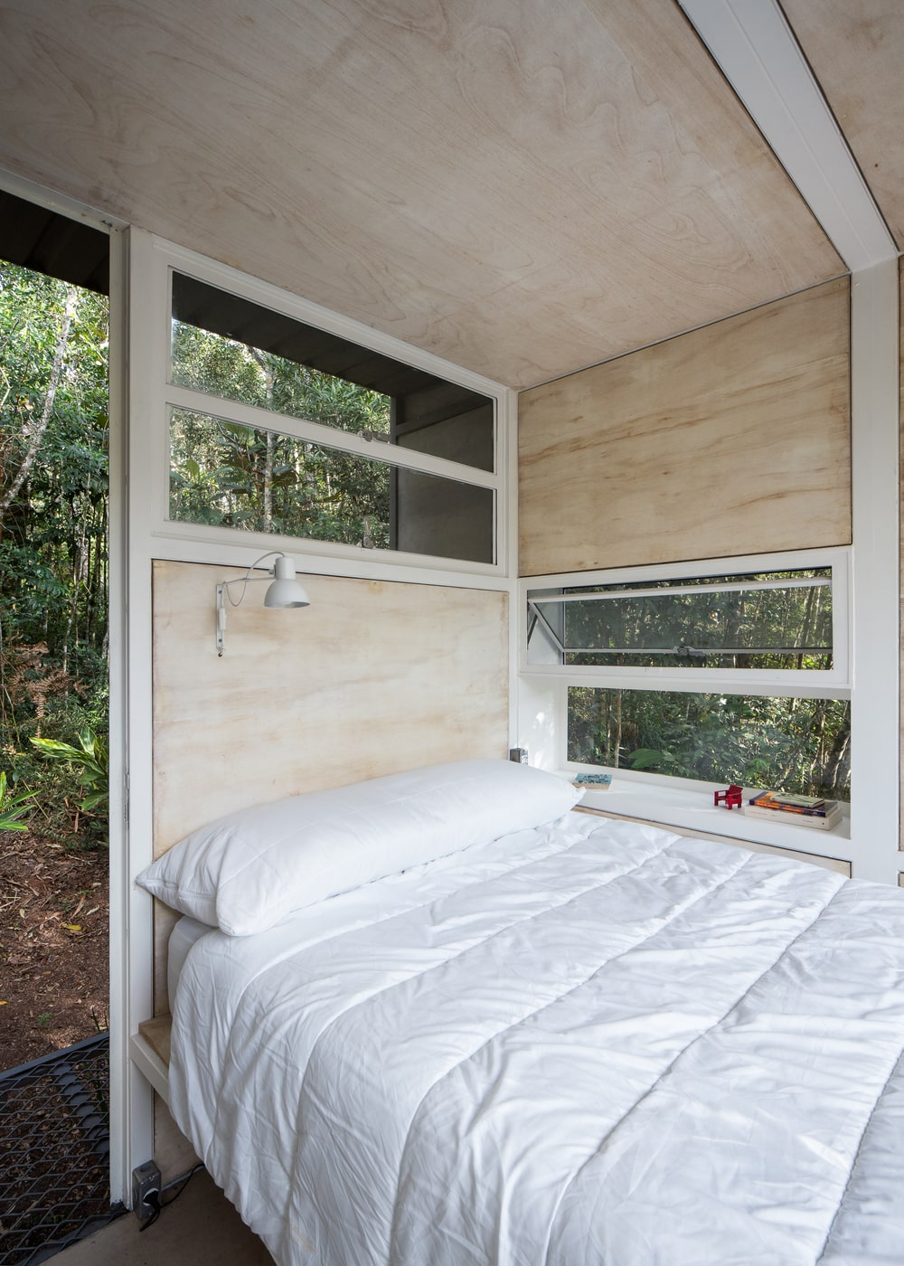 This is the bedroom that has a white bed on a built-in wooden structure that connects to the walls adorned by windows that show the landscape outside.
