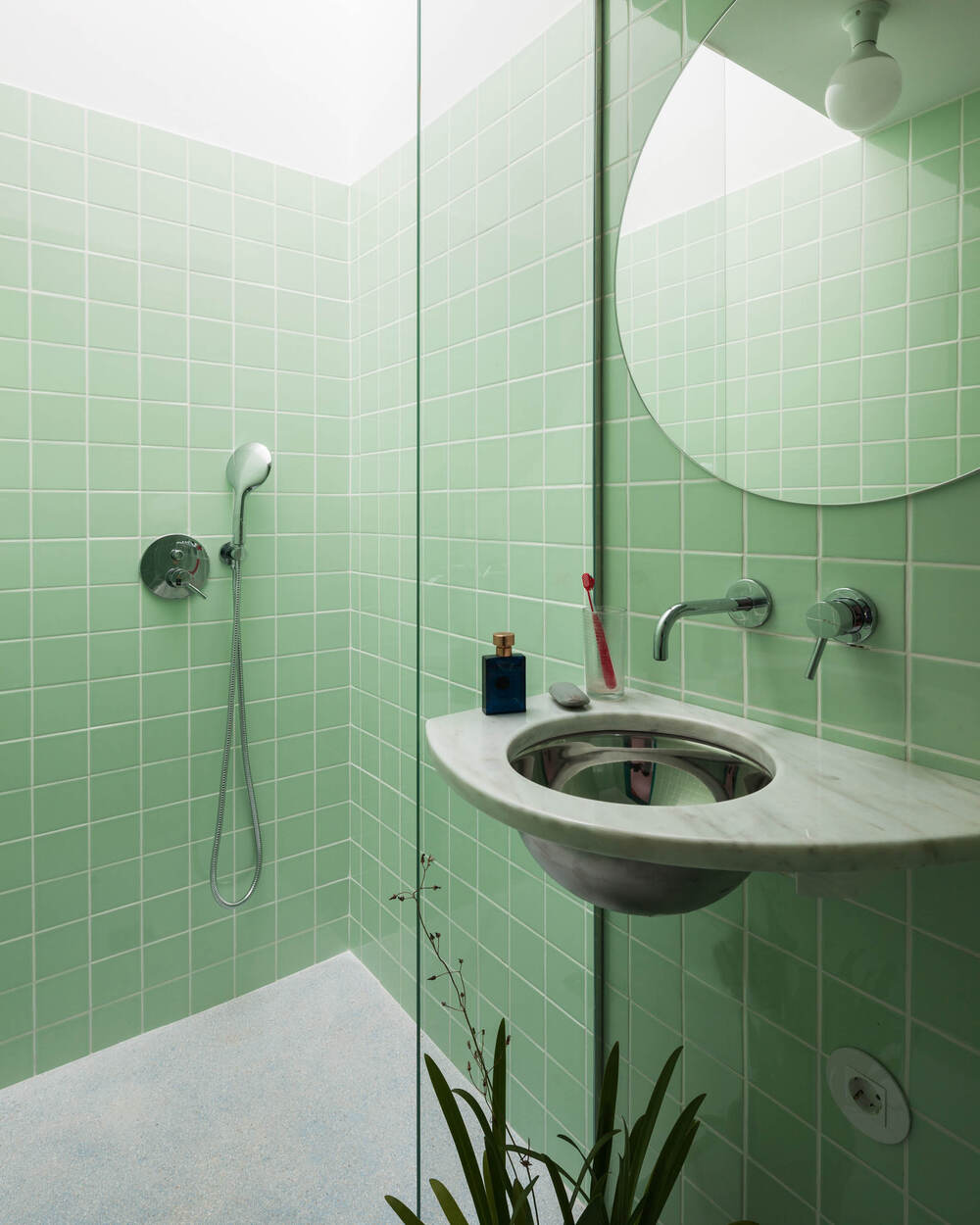 The bathroom has consistent green tiles on its walls that make the fixtures stand out.