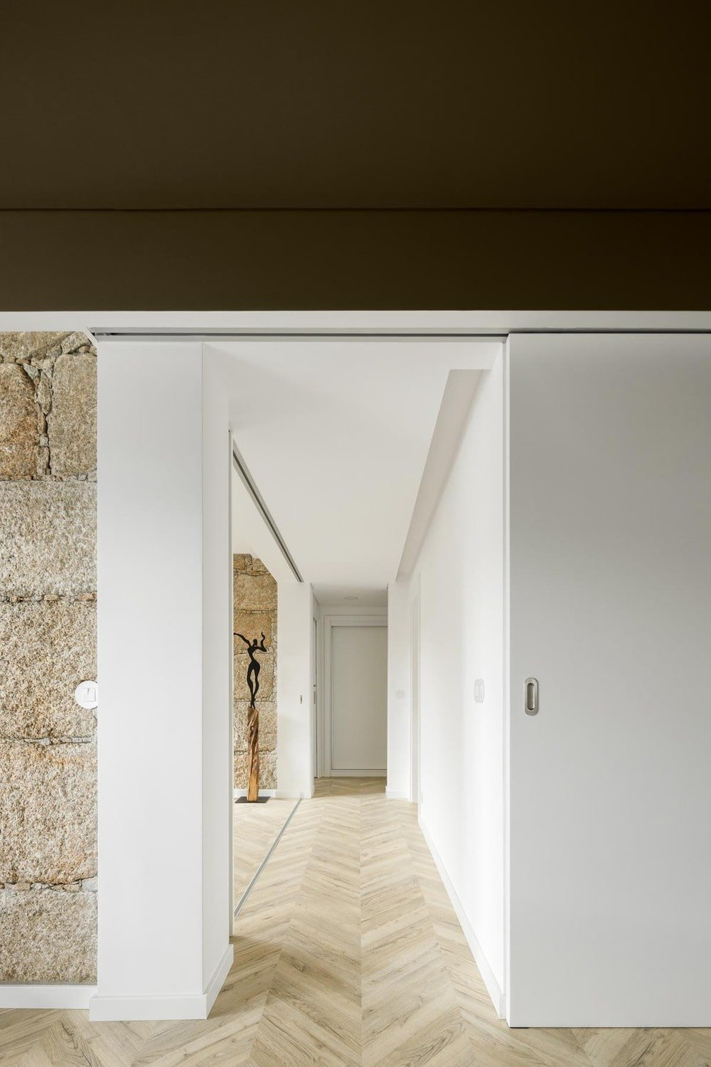This is a view of a hallway with herringbone marble flooring and white walls.
