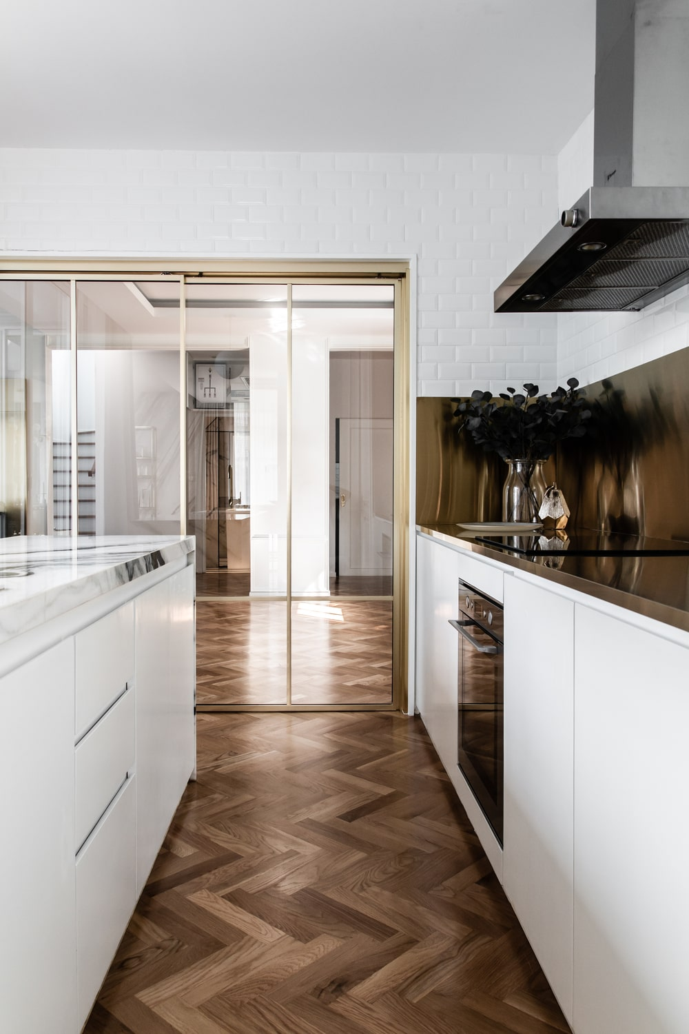 This is a view of the kitchen showcasing the proximity of the white marble kitchen island to the kitchen counter.