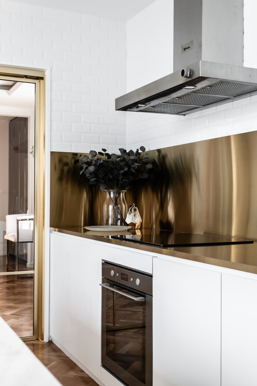 The kitchen counter has a unique look to its white cainetry, golden backsplash and stainless steel vent hood combination.