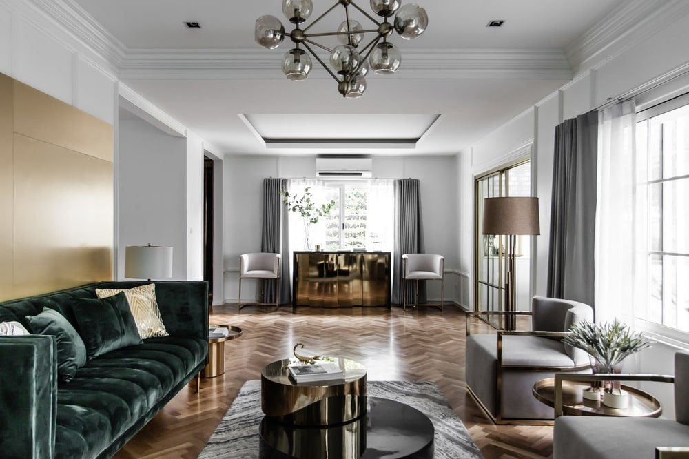 The living room has a herringbone pattern to its hardwood flooring contrasted by bright walls and ceiling.