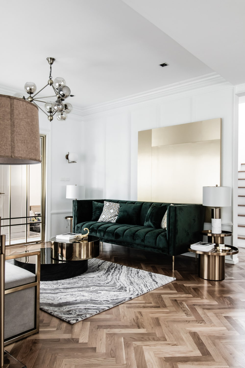 The light tone of the area rug is contrasted by the black velvet sofa.
